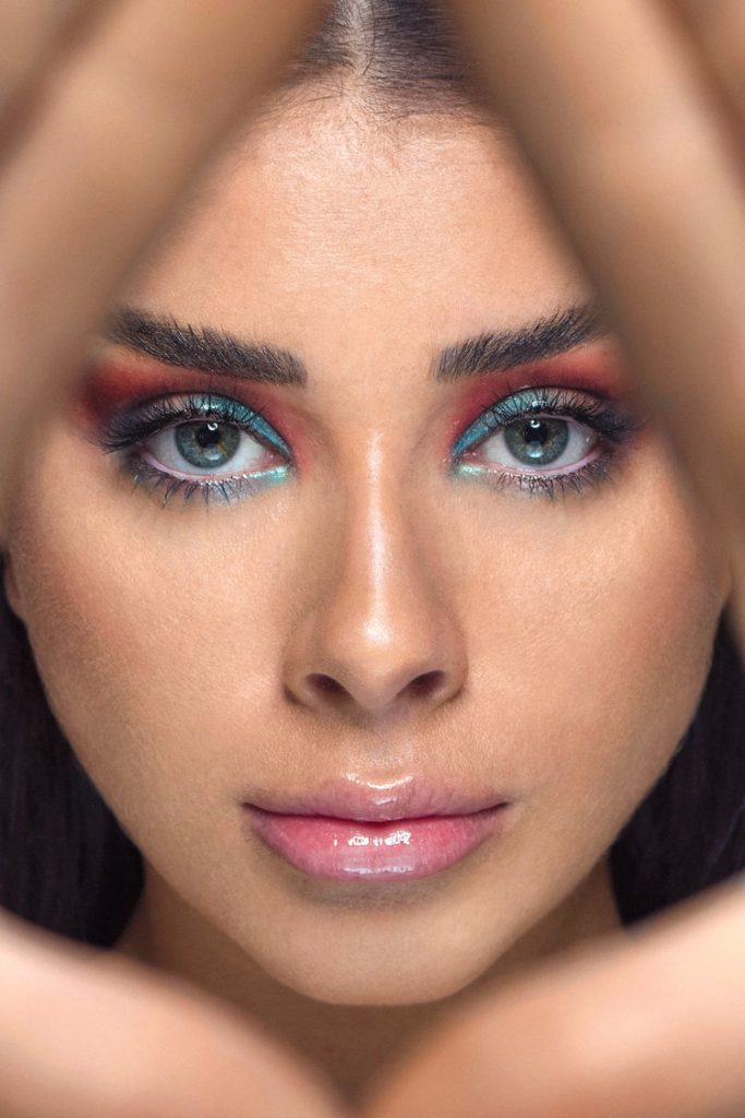Model Alivia Celio with blue and red eyeshadow looking through her hands.