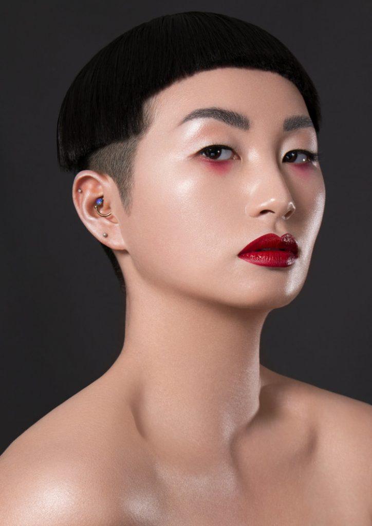 Anne He wearing red eyeshadow under the eyes and a bold red lip by Katie Saarikko.