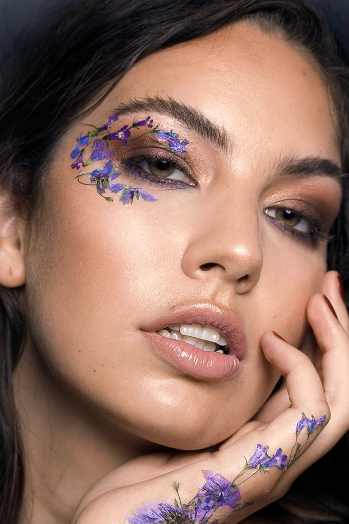 Model is Dimitra Lyras, wearing blue and purple flowers on her face and hand.