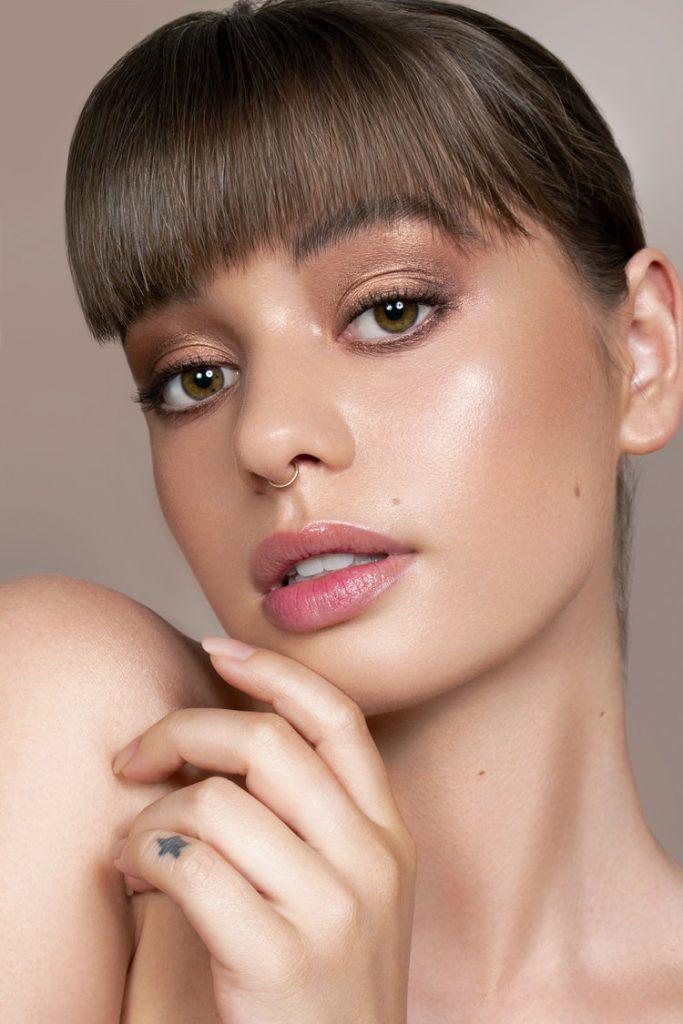 Model Jordan De Alvia wearing bronze eyeshadow with her finger on her chin.