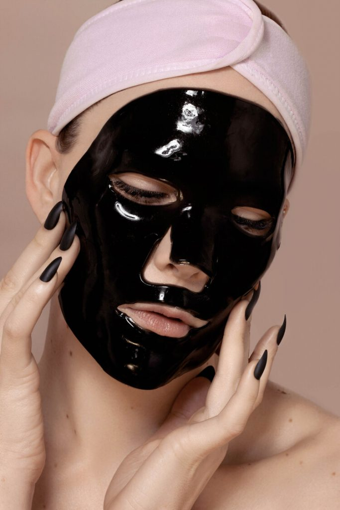 Samantha Lear with a black gel face mask and a pink headband.
