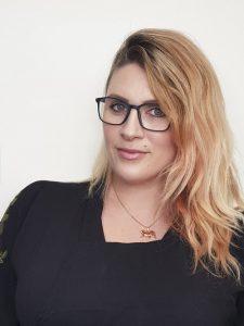 Makeup artist Katie Saarikko in a black top wearing black glasses