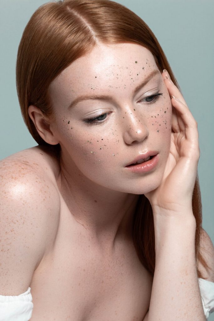 Alexandra Rayne of Devojka Models with glitter on her face.