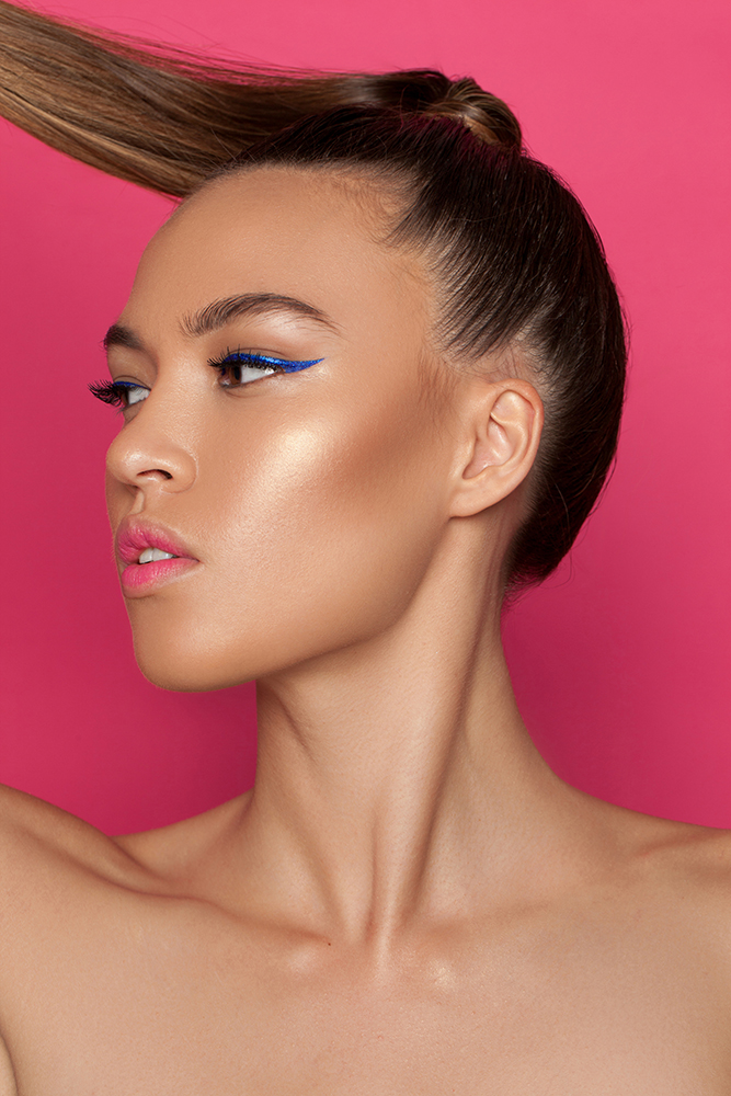 Model Sinead Carpenter with a high tight ponytail swishing to the side. The background is pink. She has blue winged eyeliner and pink lips.