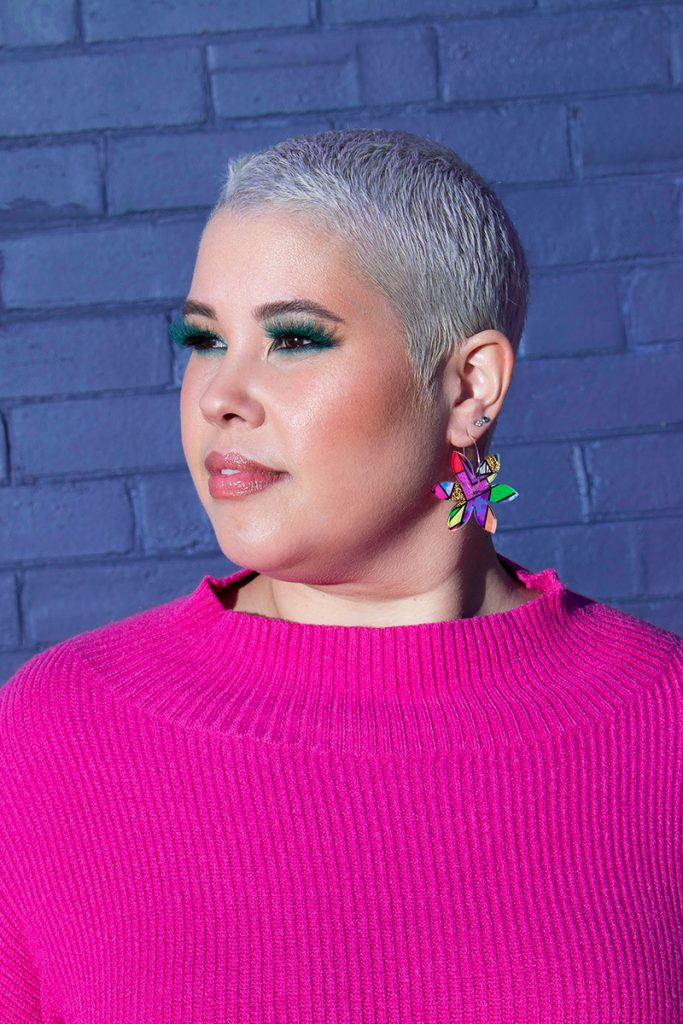April Watson wearing green eyelashes with a pink knit jumper, brightly coloured earrings and a shaved head.