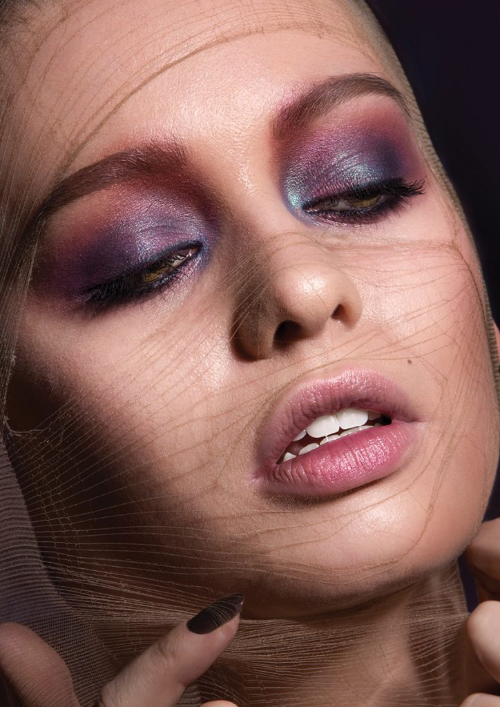 Model Jordan De Alvia with purple eyeshadow and a sheer stocking over her face.